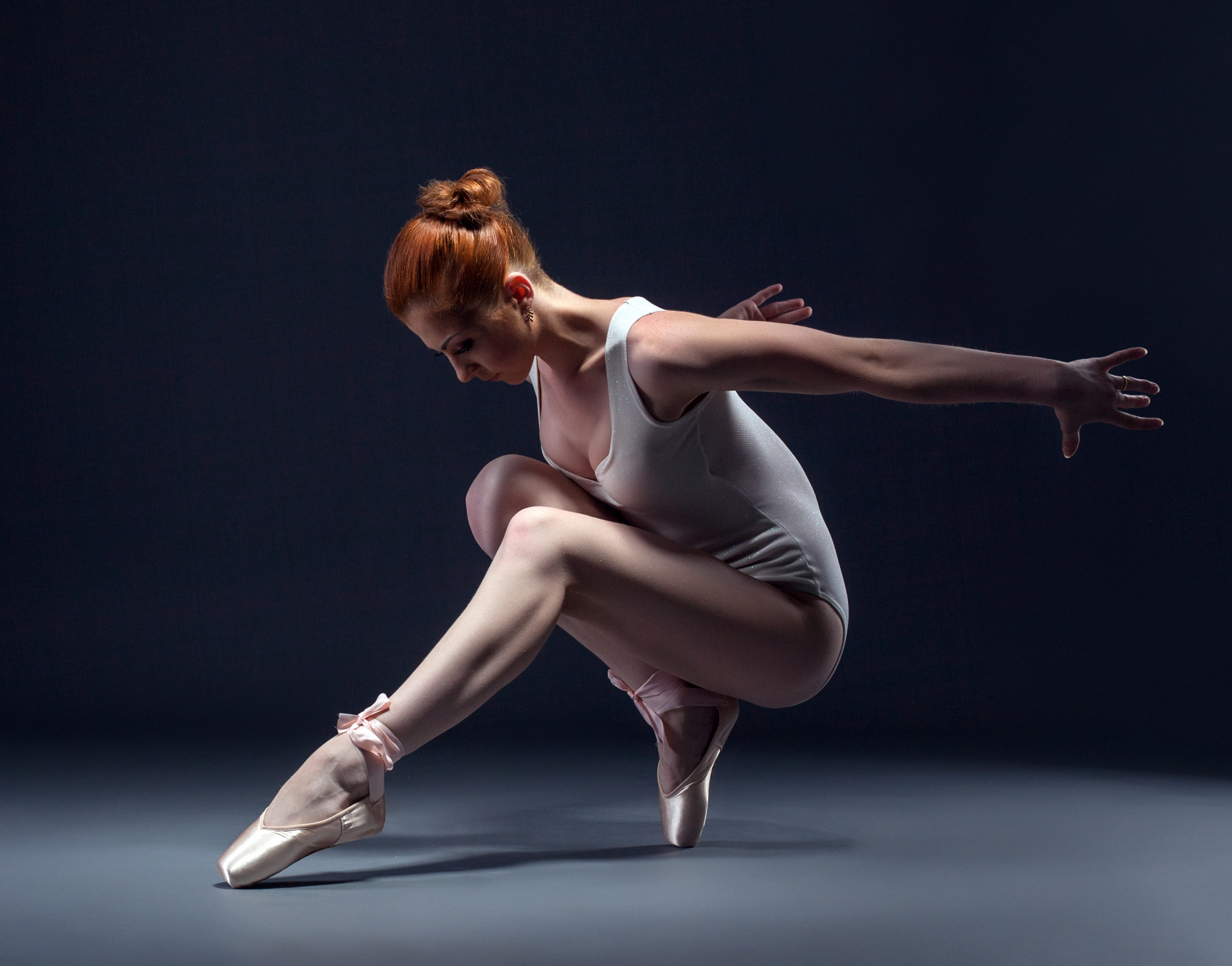 Graceful slender ballerina dancing in studio, close-up