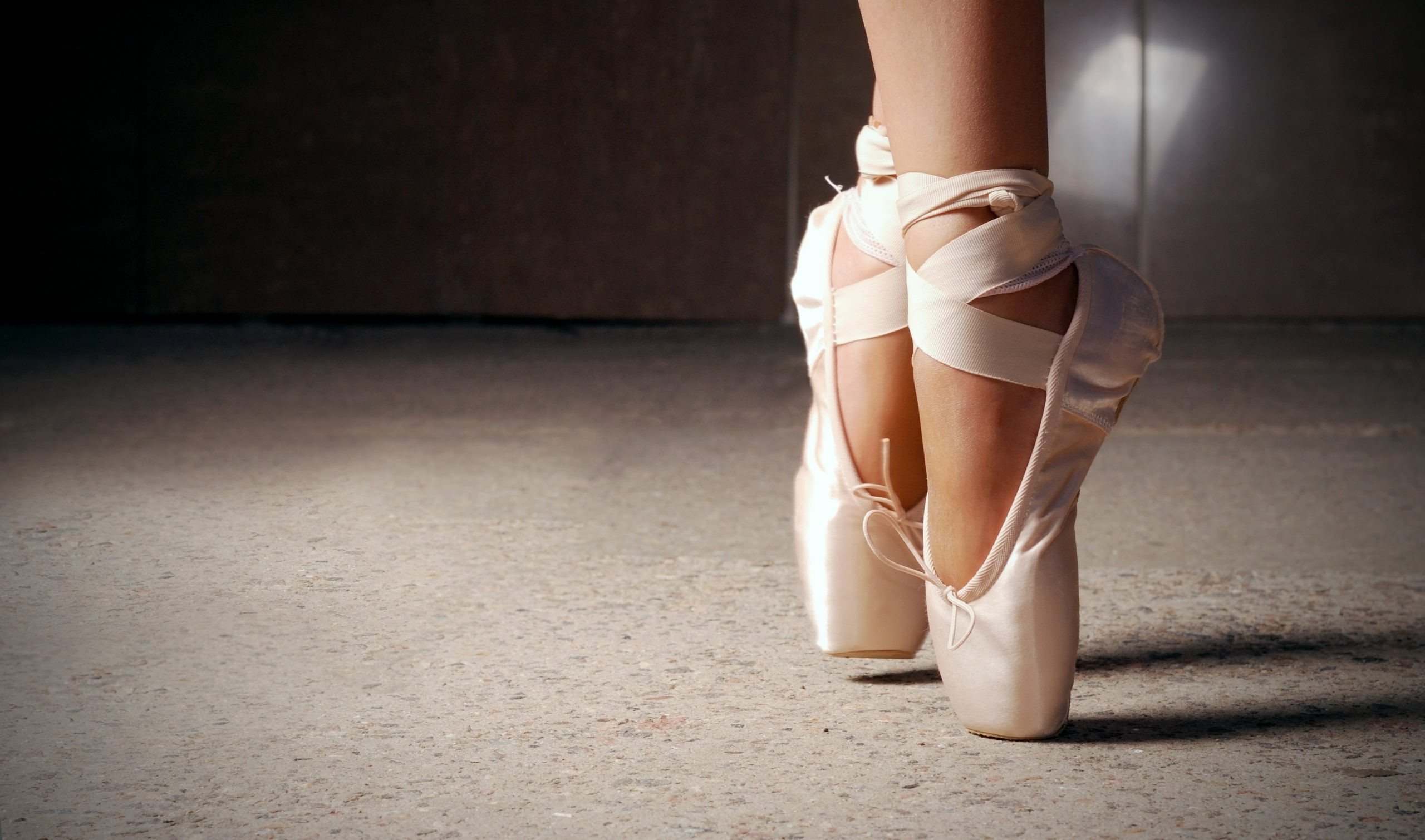 Feet of ballerina dancing in ballet shoes over a dark background