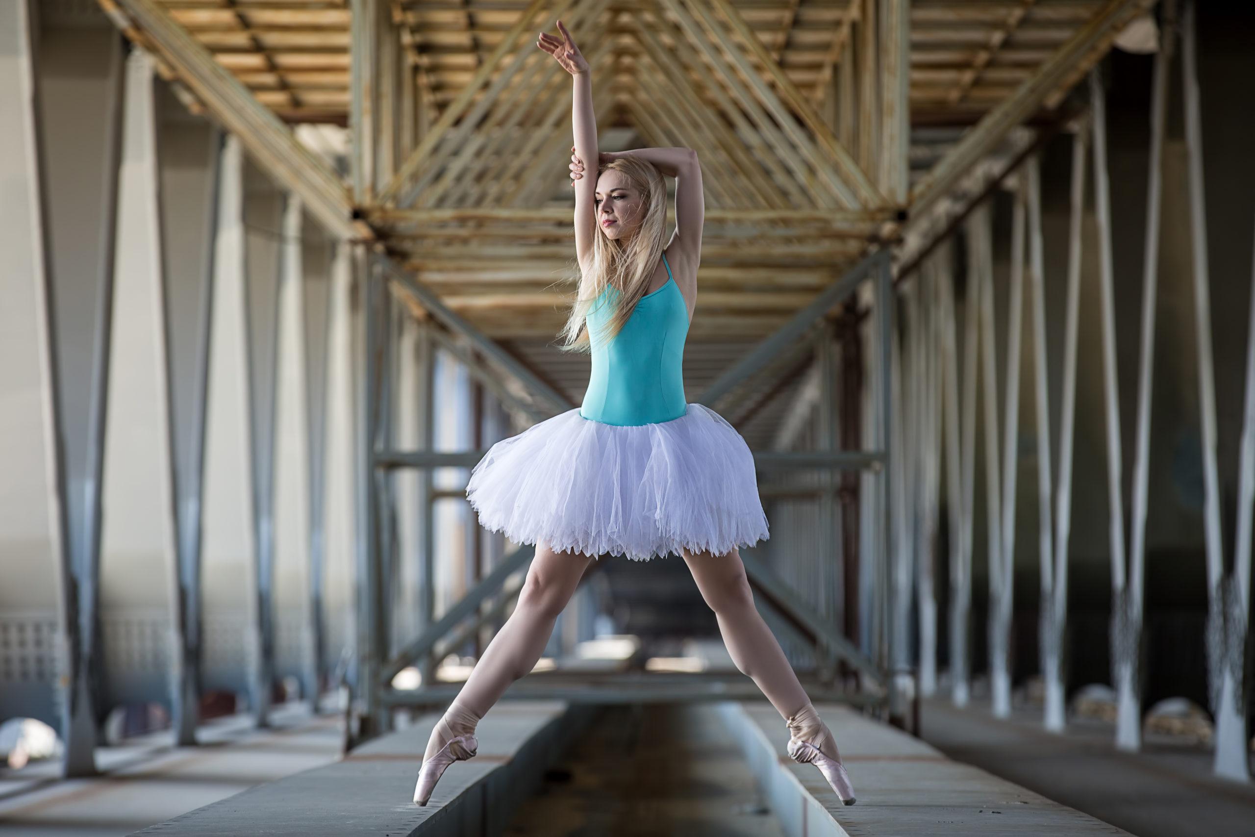 Graceful ballerina in white tutu in the industrial background of the bridge.