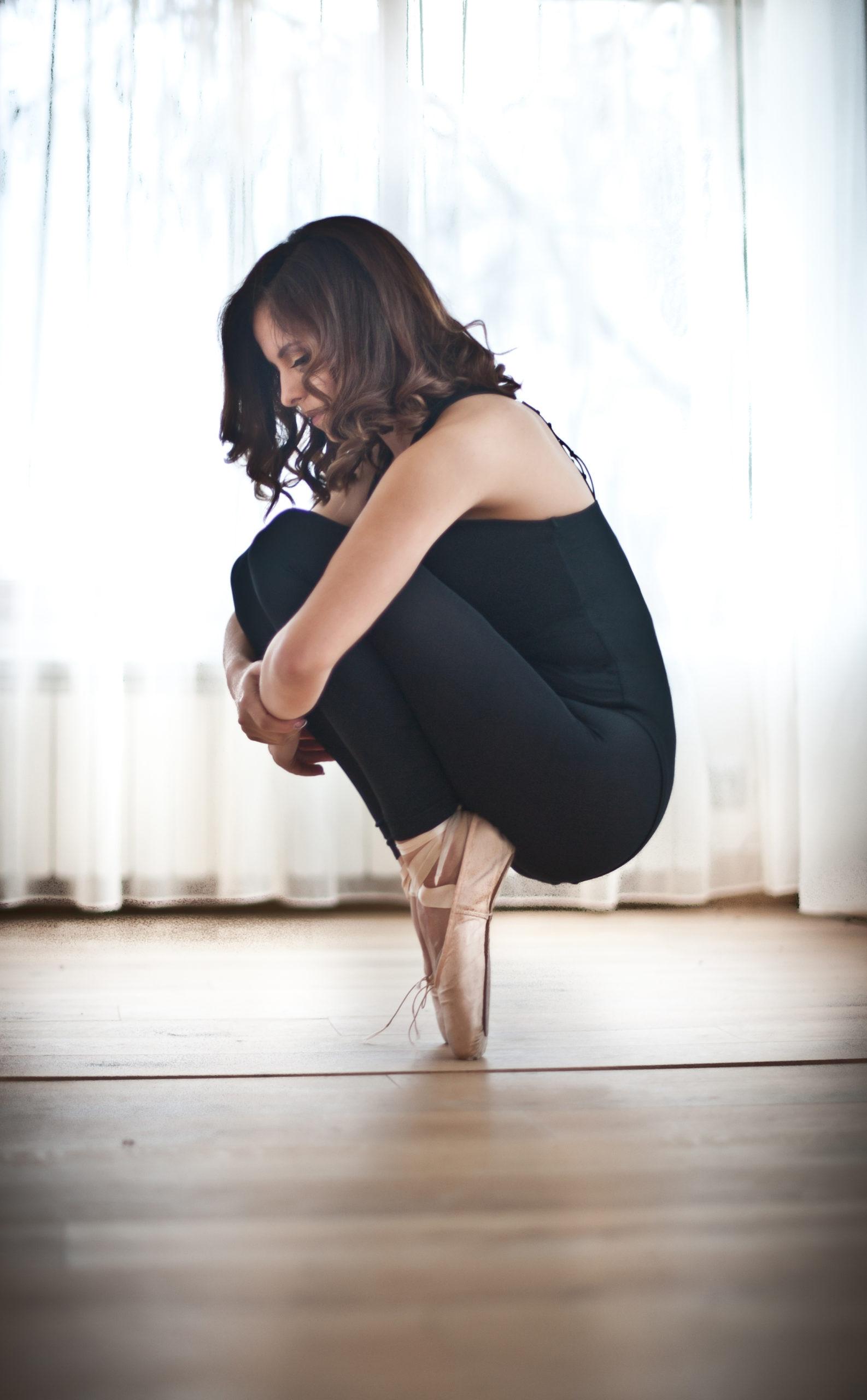 Eine Frau befindet sich in der Hocke, auf den Spitzen ihre Spitzenschuhe balancierend. Sie hat die Arme um die Beine geschlungen.