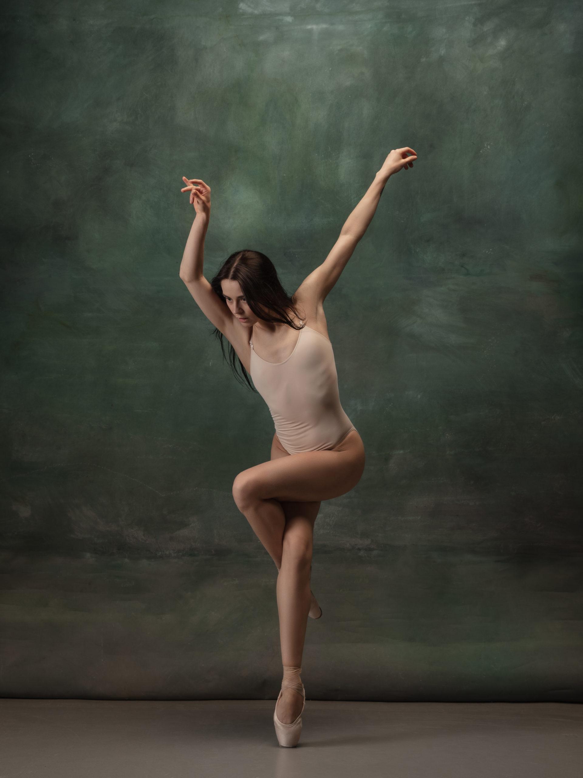 Young graceful tender ballerina on dark green studio background @ vova130555@gmail.com