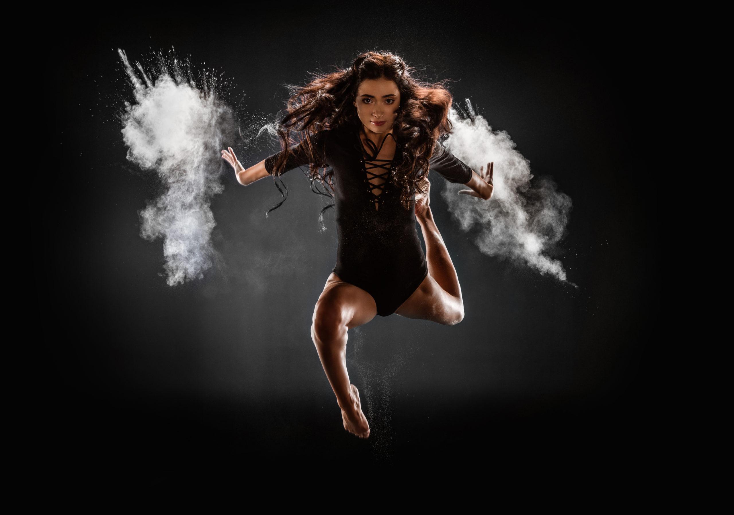 Beautiful ballerina in black bodysuit with talc jumping on dark background