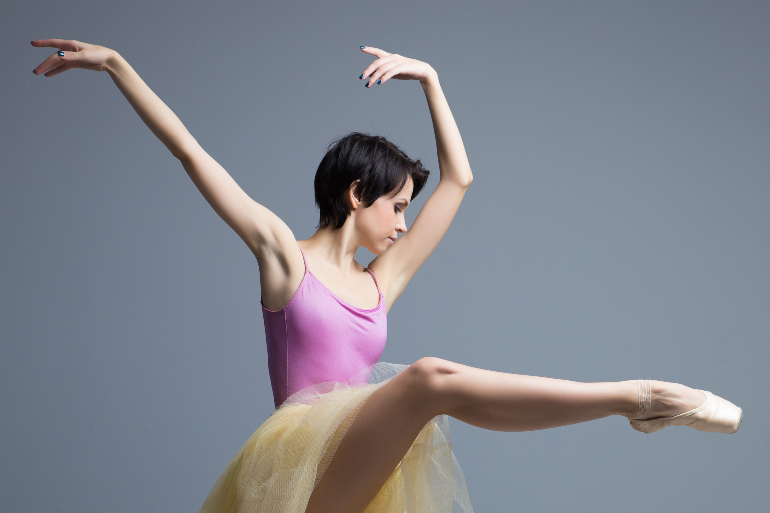 ballerina is dancing in the studio on a gray background.