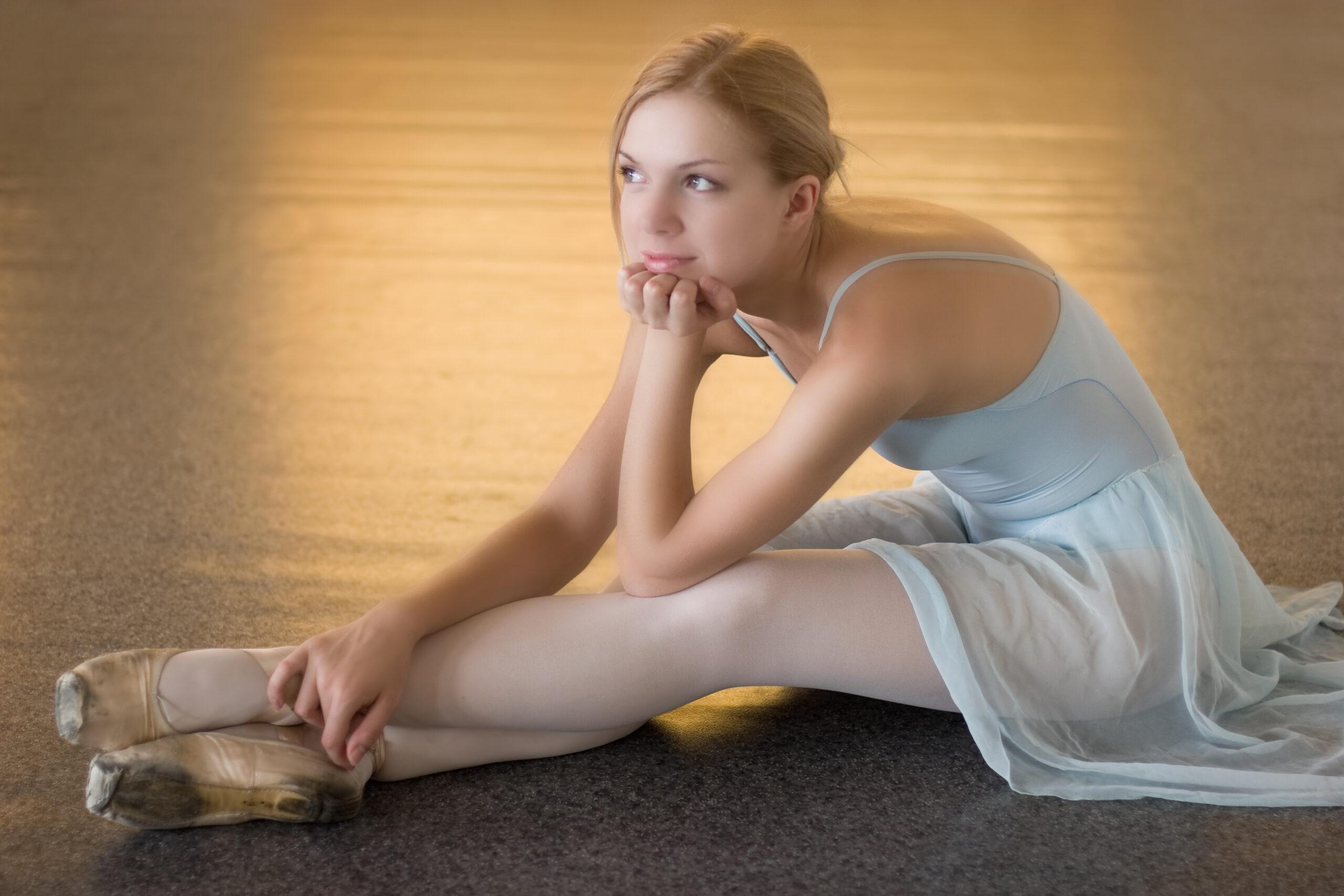 bored ballerina is siting on the floor
